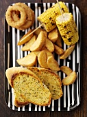 Garlic bread, chips, corn on the cob and battered onion rings