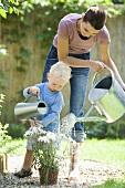 Mutter und Sohn gießen die Blumen im Garten