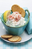 Prawn dip with crackers and sliced lemon