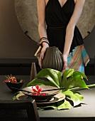 Beleuchtete Blume auf Schale mit Blumenblatt und Frau mit Vase in der Hand