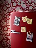A red fridge door with postcards and sticky notes
