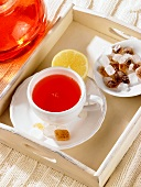 A cup of rosehip tea with candied sugar and lemon on a tray