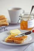 Orange marmalade being spread on toast