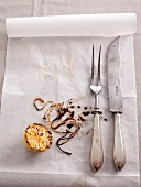 Parchment paper with a carving knife and fork, grilled lemons and twine