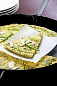 Asparagus-ricotta frittata, sliced in a pan