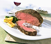 Roast beef with a pepper crust with herb butter and polenta