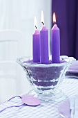 Purple candles in purple sand