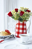 A jug being used as a vase with tea and cake with redcurrants