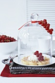 A waffle with cream and redcurrants under a cloche