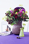 An autumnal bouquet in a purple vase