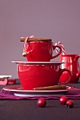 A red espresso cup and a coffee cup with cinnamon sticks