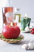 A tomato-shaped candle on a scallop shell dish as table decoration