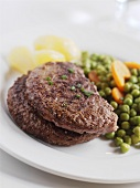 Hamburger steaks with peas and carrots