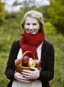 Woman holding basket of freshly picked apples