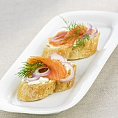 Baguette slices topped with smoked salmon, onions and dill