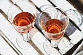 Two glasses of rosé wine on wooden chair