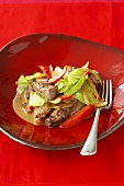 Pieces of beef in pepper sauce with cabbage and red peppers