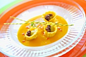 Butternut squash soup with cep ravioli and truffle pearls