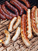 Various types of sausages on a charcoal barbecue