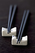 Black chopsticks on porcelain rests