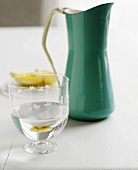 Glass of water in front of enamel jug