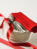 Stack of plates, forks, red napkins and ribbon