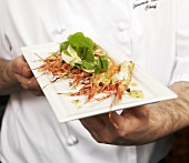 Chef holding prawns with cress salad