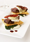 Beefsteak with spinach and melted cheese (appetiser)