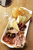 Appetiser platter: cold cuts, cheese, olives, fruit & white bread