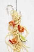 Spaghetti with prawns and sesame seeds hanging on a hook