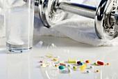 Verschiedene Pillen, Brausetablette und Hantel