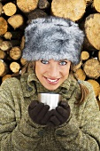 Young woman in winter hat holding cup, stack of wood behind