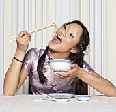 Asian woman eating with chopsticks