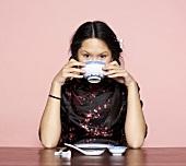 Asiatische Frau isst aus Schälchen
