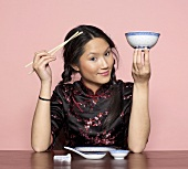 Asian woman holding chopsticks and bowl