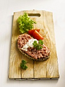 Slice of bread with minced meat on chopping board, close-up