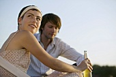 Young couple with drink on a roof terrace