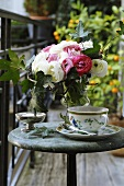 Vase of ranunculus and cup and saucer on table on balcony