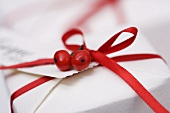 Parcel with red gift ribbon and holly berries