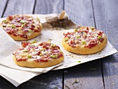 Three small ham and spring onion pizzas
