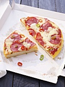 Salami pizza with chilli rings on pizza box
