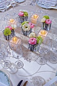 Table decoration of ranunculus, tealights and glass beads