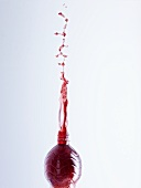 Cherry juice splashing out of a bottle