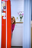 Little girl hiding behind refrigerator