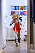 Little girl riding scooter through flat