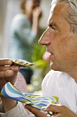 Grey-haired man eating an oyster