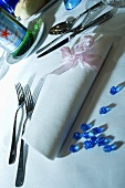 Place-setting with fabric napkin and blue glass gems
