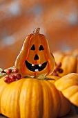 Pumpkin with amusing face and rowan berries