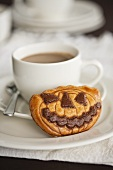 A cup of coffee with a pumpkin biscuit for Halloween