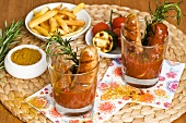 Currywurst (sausages with curry sauce) in glasses, chips